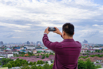 Young man taking photo of cityscape with his cellphone