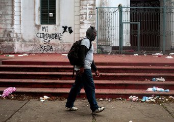 """A pro-government supporter walks past a graffiti, which reads: """"My commander stays"""", in reference to Nicaragua's President Daniel Ortega, in Diriamba"""