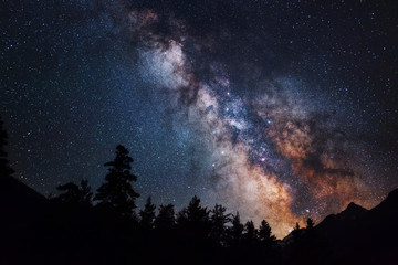 Astrophotography of Milky Way galaxy. Silhouette of mountains. Stars, nebula and stardust at night sky landscape