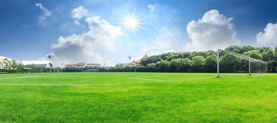 Green football field under blue sky background