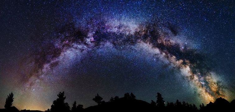 Panoramic astrophotography of whole visible Milky Way galaxy. Silhouette of mountains. Stars, nebula and stardust at night sky landscape