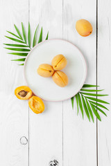 Ripe apricots on a round plate on a white board table..