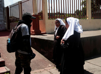 A pro-government supporter speaks with nuns in front of a church in Diriamba