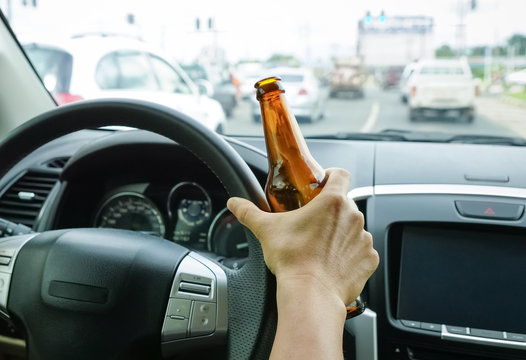 A driver holding alcoholic bottle while driving / Drunk driving concept