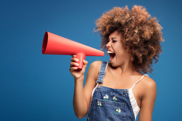 Afro young girl screaming by red megaphone.