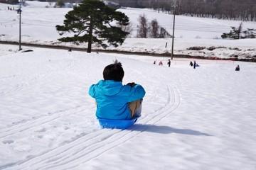 スキーリゾートでソリ遊びをする子供