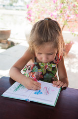 Adorable little girl drawing artwork top view on crayons in a notebook, Baby healthy and preschool concept