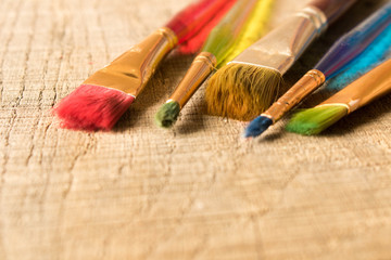 Different brushes on the old wooden table . Selective focus. Creative concept