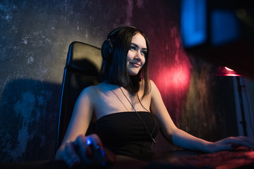 girl gamer in headphones and with mouse and keyboard in her hands playing network games preparing to participate in international competitions in e-sports