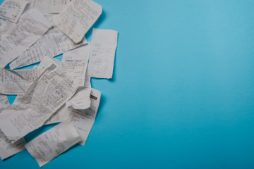 Pile of shopping receipts on blue background