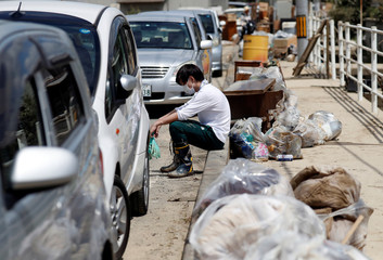 A local resident pauses as he tries to clean debris at a flood affected area in Mabi town in Kurashiki