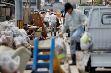 Local residents try to clean debris at a flood affected area in Mabi town in Kurashiki