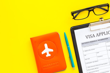 Fill visa application form. Form near glasses, pen, passport cover with airplane sign on yellow background top view space for text