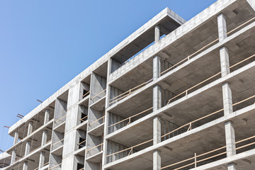 high-rise concrete building under construction against blue clean sky background
