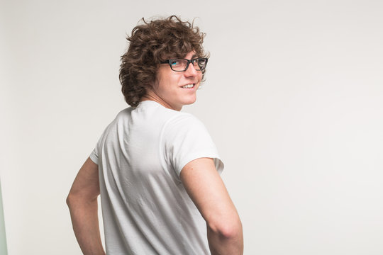 Young man in white t-shirt and glasses turning back at the camera in studio.