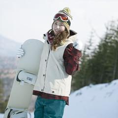 スノーボードを持ち微笑む女性