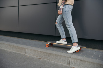 cropped image of tattooed woman skateboarding at street
