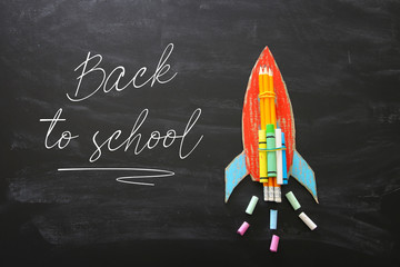 Back to school concept. Top view image of handmade cardboard rocket and clouds with pencils over classroom blackboard background