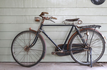 Close-up old Ancient bicycle on the background of a gray wooden wall.