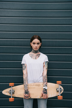 Serious tattooed girl holding skateboard and looking at camera against black wall