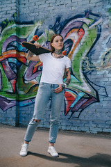 attractive girl with tattoos holding skateboard over shoulder near wall with graffiti
