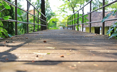 Old wooden bridge with metal rail in public park.