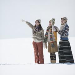 雪原で遠くを指差す3人の女性