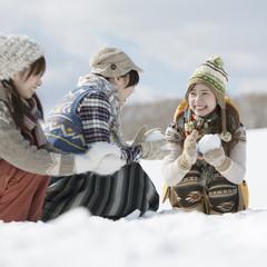 雪原で雪玉を作る3人の女性