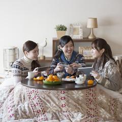 こたつでゲームをする3人の女性
