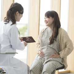 エコー写真を持ち話をする女医と妊婦