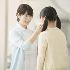 女の子と話をする看護師