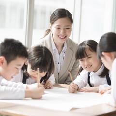 グループ学習をする小学生と先生