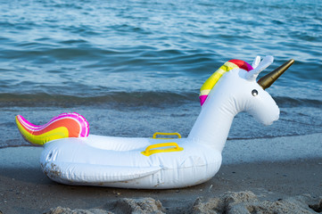 Inflatable unicorn on the beach in the background