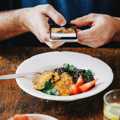 Man vegetarian taking pictures food that he eats on smartphone