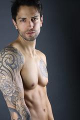Handsome man model posing shirtless on gray background