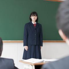 黒板の前に立ち微笑む女子学生