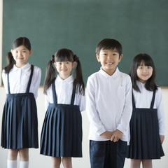 黒板の前に並ぶ小学生