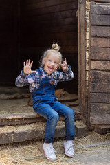 kid sticking tongue out and sitting on stairs of stable