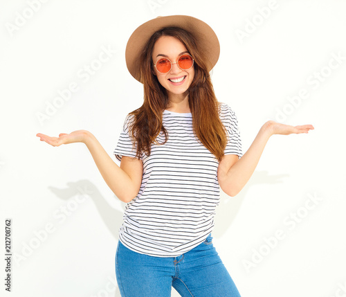 89812609 Young brunette woman in casual hipster clothes and brown hat displaying  something on both flat hands for similar choice of product, isolated on  white.