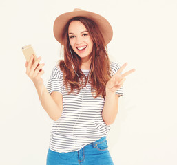Portrait of a pretty girl in summer hipster clothes taking a selfie isolated on white background. showing peace sign