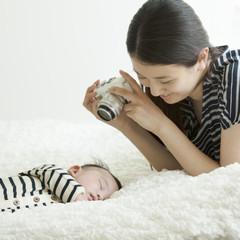 眠る赤ちゃんと見守る母親