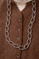 Extreme close up chain necklace on brown coat. Vertical view suit with accessorie.
