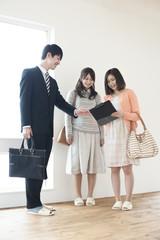 部屋の内見をする2人の女性とビジネスマン