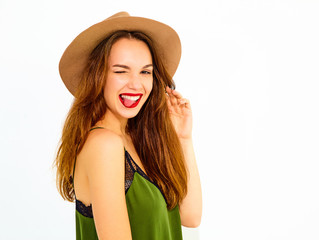 Young stylish girl model in casual summer green clothes and brown hat with red lips. Winking and showing her tongue