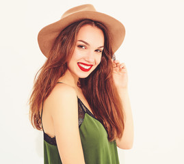 Young stylish girl model in casual summer green clothes and brown hat with red lips, posing near white wall