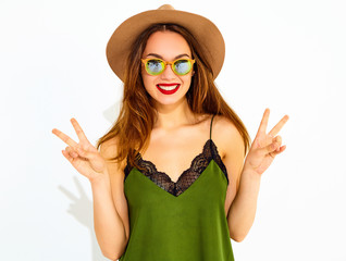 Young stylish girl model in casual summer green clothes and brown hat with red lips, showing peace sign