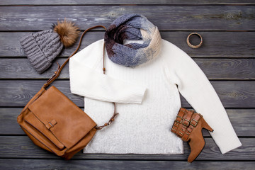 Casual winter women's clothes. Beauty feminine clothes arrangement with hat, handbag, sweater, scarf. Flat lay, top view.