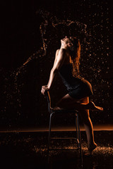 Girl in black dress on chair in water in a small pool, drops of water and dark background