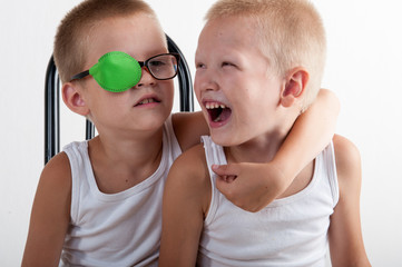 Two happy children play together in room. Boys brothers on white background. Сhild in glasses with green occluder. Ortopad Boys Eye Patches Nozzle for glasses to treat strabismus (lazy eye)