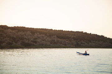 A young man is riding a kayak. Quiet waters and bright sun.
